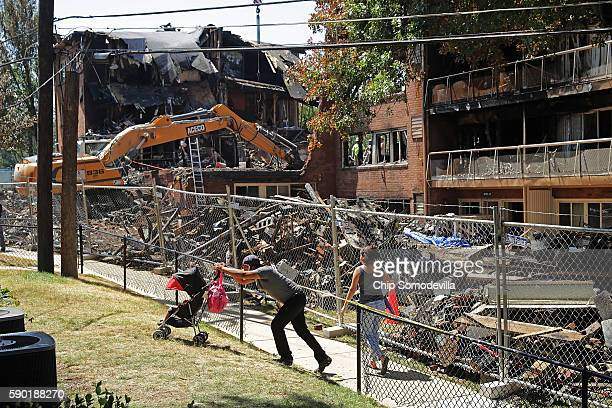 Residents of the Flower Branch Apartments walk past the section of the complex that exploded and burned last week as investigators continue to comb...