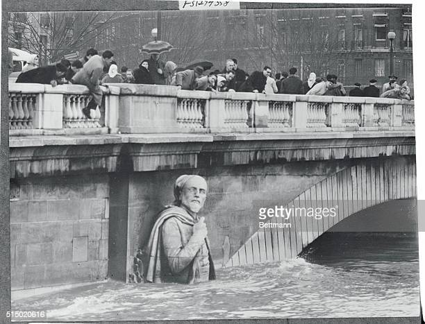 Residents of the French capital lean over the parapet of the Alma Bridge to see how high flood waters of the river Seine have reached on the giant...