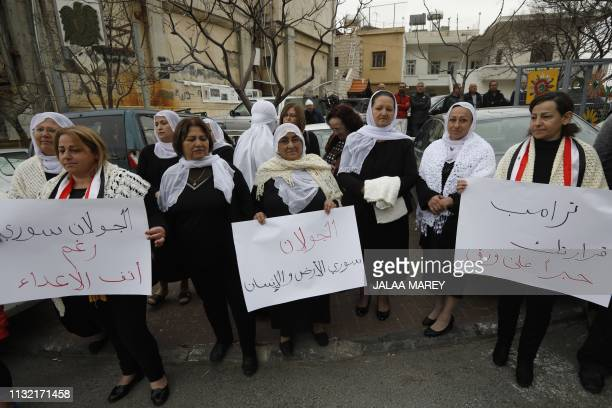 Residents of the Golan Heights raise Syrian and banners during a protest against the backing of Israel's capture of the Golan Heights by the US...