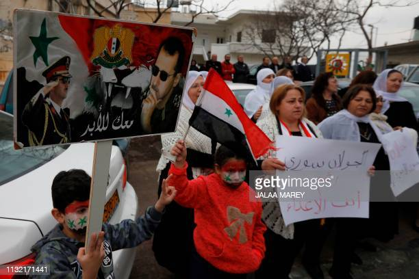 Residents of the Golan Heights raise Syrian flags and a banner with portraits of the Syrian President Bashar alAssad during a protest against the...