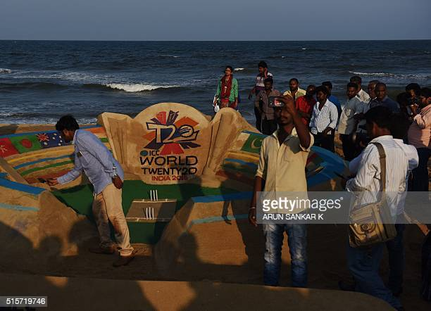 Residents of the Indian southeastern city of Chennai look at a sand artist giving the finishing touches to a sand sculpture he put up using the ICC...