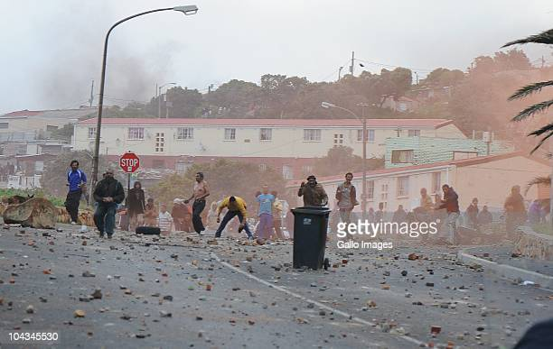 Residents of the informal settlement Hangberg throw stones at police after violence broke out in Hout Bay near Cape Town South Africa on 21 September...