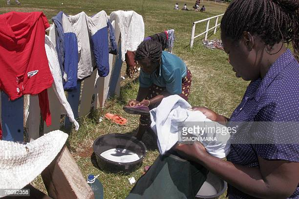 Residents of the Kibera slum wash their clothes in the open air after they found a new shelter at the Jamhuri grounds in Nairobi 02 January 2008...