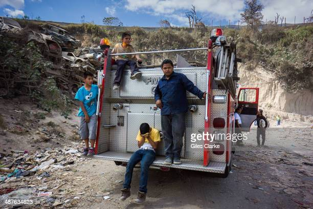 Residents of the landfill community stand on a fire truck January 14 2014 in Guatemala City Guatemala The bomberos voluntarios are a volunteer fire...