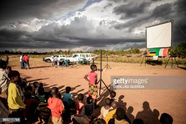 Residents of the northern Mozambique village of Alua look at a giant screen being set up ahead of watching a live broadcasting of the Football World...