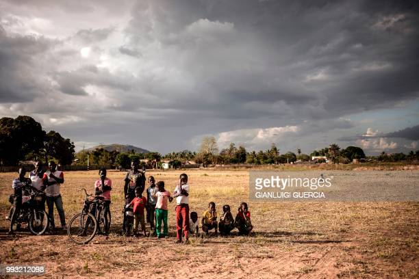 TOPSHOT Residents of the northern Mozambique village of Alua look at a giant screen being set up ahead of watching a live broadcasting of the...