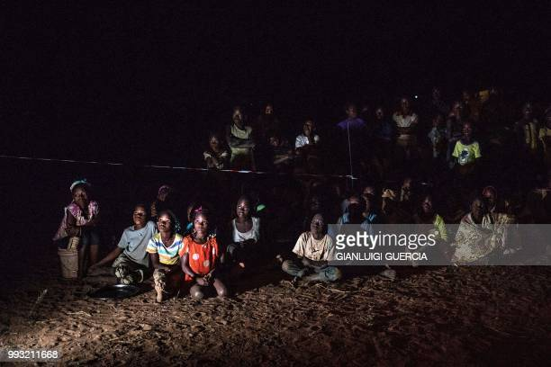 Residents of the northern Mozambique village of Alua react as they watch a cartoon during a break of a live broadcasting of the Football World Cup...