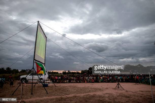 Residents of the northern Mozambique village of Alua watch a live broadcasting of the Football World Cup quarter final match organised by the Italian...