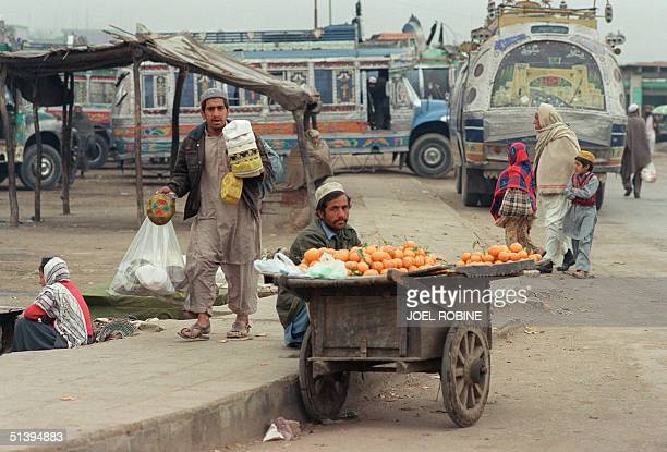 Residents of the northern Pakistan city of Peshawar gather 14 February 1989 at the market of the city