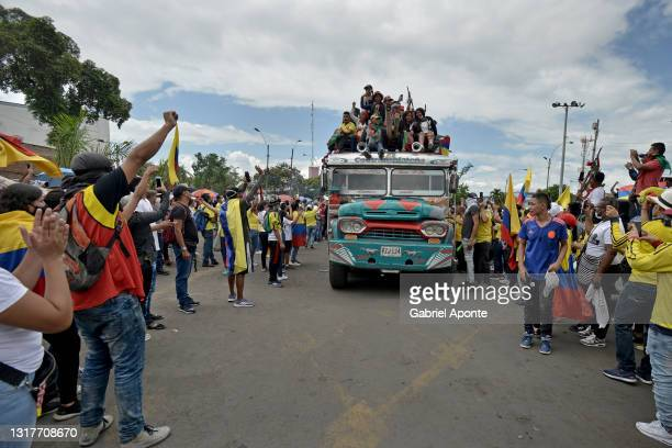 Residents of the Puerto Resistencia sector wave Colombian flags as they thank the Indigenous Minga for their presence in the city as they pass...