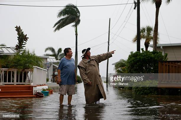 Residents of the Sandpiper Resort survey the rising water coming from the Gulf of Mexico into their neighborhood as winds and storm surge associated...