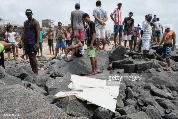 Residents of the site observe a piece of the helicopter that the sea threw on the rocks near the scene of the accident in Recife Northeast Brazil on...