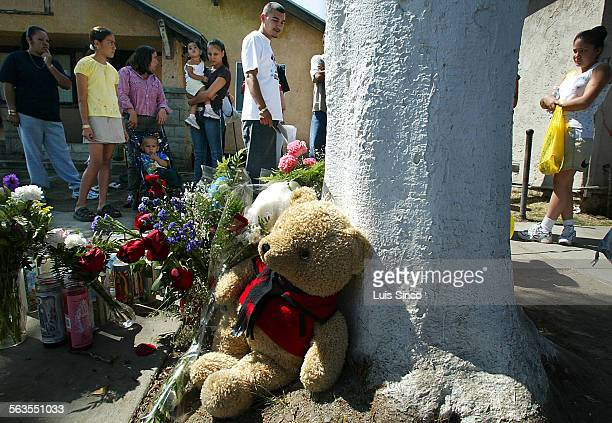 Residents of the South Los Angeles neighborhood near the intersection of Compton Ave and E 69th Street gather around a makeshift memorial at the base...