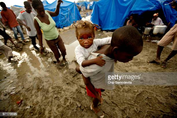 Residents of the Tapis Vert internally displaced persons camp navigate the mud and sewage after overnight rains soaked the tent village February 28...