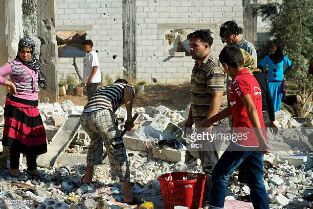 Residents of the town of Khaweija in northcentral Syria clean up the damage from a Syrian government airstrike September 16 2012