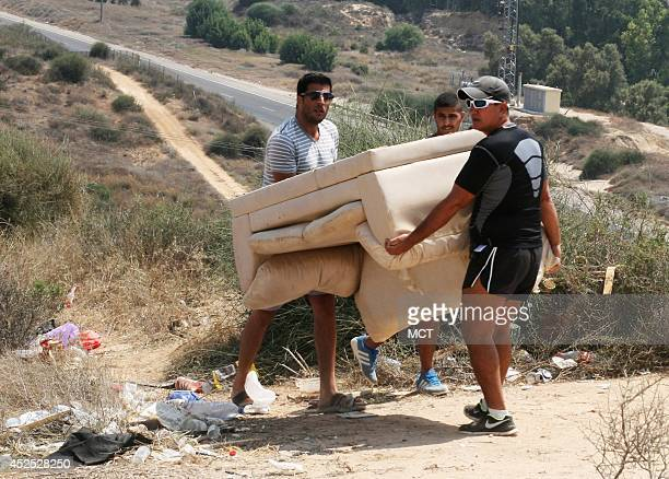 Residents of the town of Sderot, Israel, carry a sofa up to a hilltop near the border community to prepare for an evening watching the Israeli army...