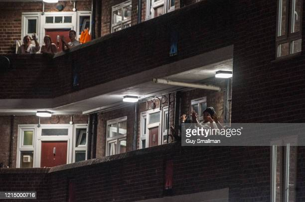 Residents of the Tulse Hill Estate in South London come out onto their balconies to applaud NHS staff fighting the virus on March 26 2020 in London...