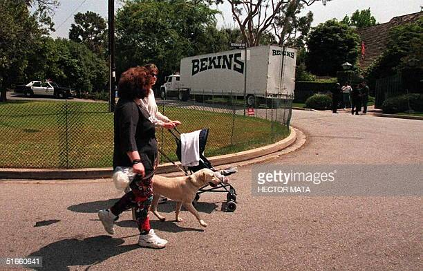 Residents of the upscale neighborhood of Brentwood CA walk past former American football star OJ Simpson's house where a moving company truck hired...