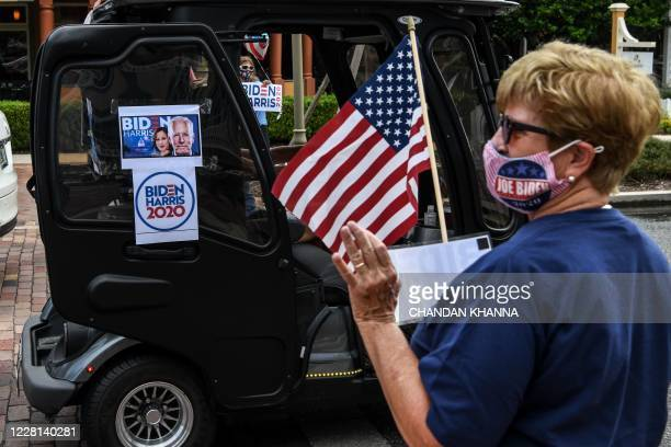"Residents of The Villages, Florida, holds a ""Biden Harris 2020"" campaign poster on August 21 as he participates in a golf cart parade to celebrate..."
