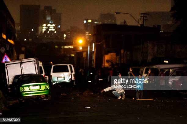 Residents of the worker's hostel in Jeppe's Town neighbourhood of Johannesburg kneel in front of police forces on February 26 2017 Violence flared up...