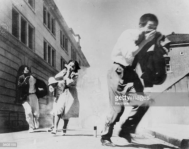 Residents of Tokyo running for shelter during a realistic enactment of an air-raid drill.
