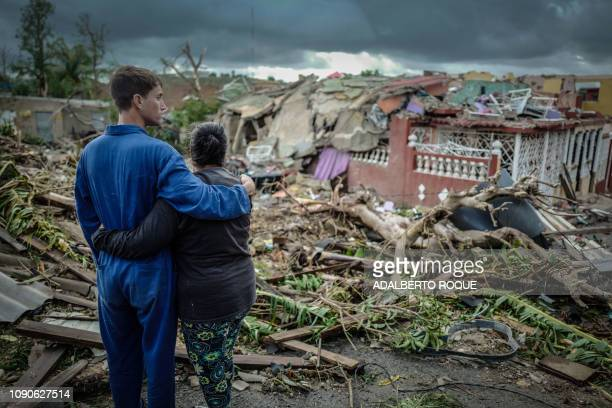 Residents of tornadohit Regla neighbourhood stand in front of their destroyed house in Havana on January 28 2019 A rare and powerful tornado that...