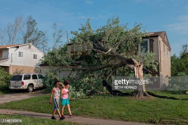 Residents of Trotwood Ohio near Dayton walk by a damaged home on May 28 after powerful tornadoes ripped through the US state overnight causing at...
