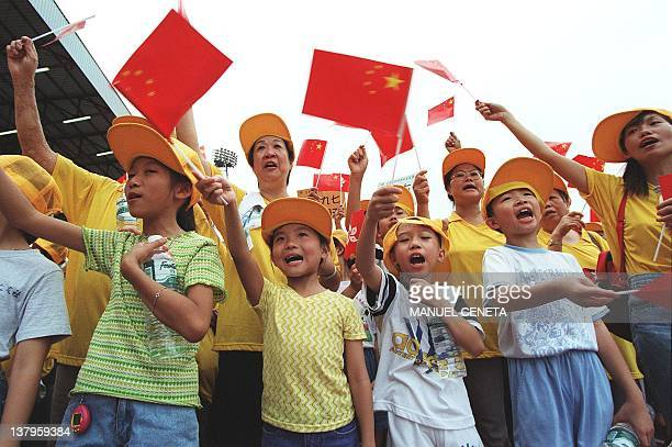 Residents of Tsuen Mun wave Chinese flags during the celebrations 22 June in Yuen Long at the New Territories to welcome the reunification of Hong...