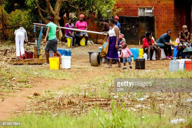 Residents of Warren Park queue for water in the Zimbabwean capital Harare on November 16 a day after the military took power and announced plans to...