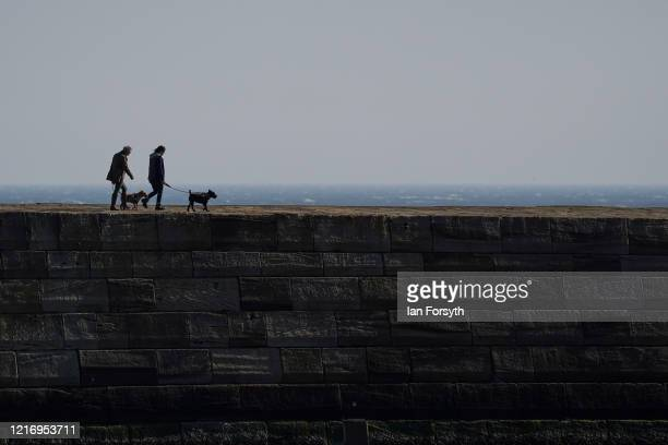 Residents of Whitby walk their dogs along the seawall as streets in Whitby remain empty as visitors observe the guidelines during the Coronavirus...