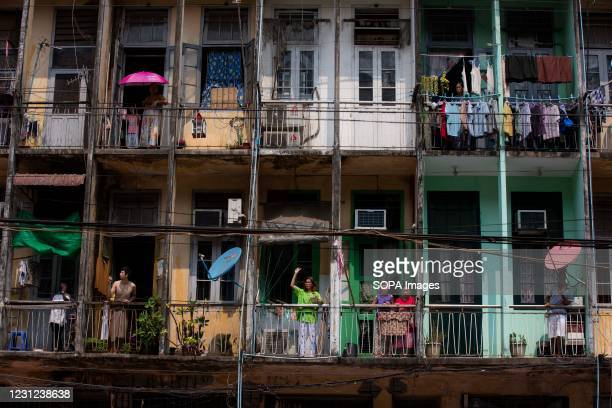 Residents of Yangon watch the protesters march from the balcony of their apartments during the demonstration. A massive crowd took to the streets of...