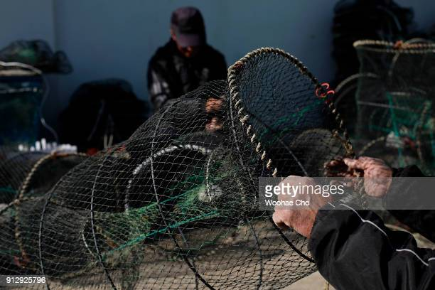 Residents of Yangyang repair their nets for fishing octopus and crabs at Namai port in Yangyang Ganwon province in South Korea on February 1 2018 The...
