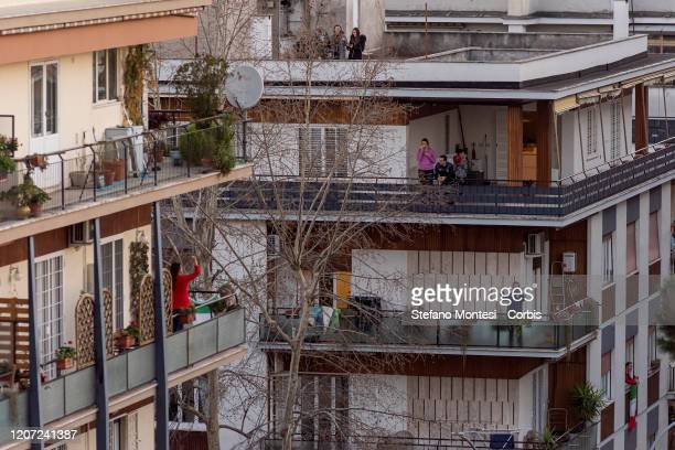 Residents on balconies sing Il cielo sempre più blu during a flash mob to raise morale as the lock down continues due to the coronavirus outbreak to...