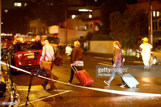 Residents on Kohimarama Road leave with overnight bags as torrential rain caused a nearby hillside to collapse and fall onto apartments Torrential...