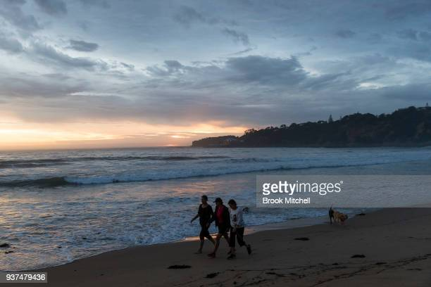 Residents on Tathra beach at sunrise on March 25 2018 in Tathra Australia A bushfire which started on 18 March destroyed 65 houses 35 caravans and...