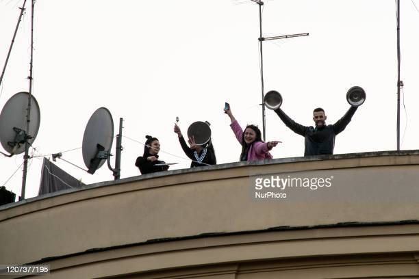 Residents on window and balconies sing 'Il cielo sempre piu blu' during a flash mob to raise morale as the lock down continues due to the coronavirus...