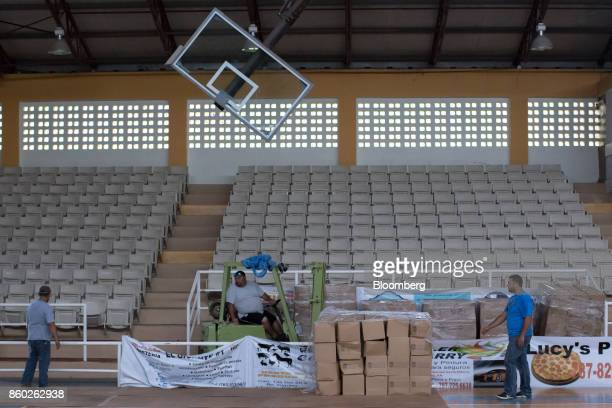 Residents organize disaster relief meals and bottled drinking water sit inside a basketball court in Adjuntas Puerto Rico on Friday Oct 6 2017 US...
