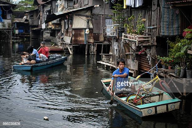 Residents paddle makeshift boats past houses partially submerged in floodwaters at the Artex compound in Malabon city north of Manila Philippines...