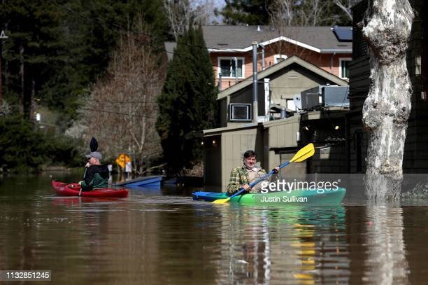 Residents paddle through a flooded neighborhood on February 28 2019 in Guerneville California The Russian River has crested over flood stage and is...