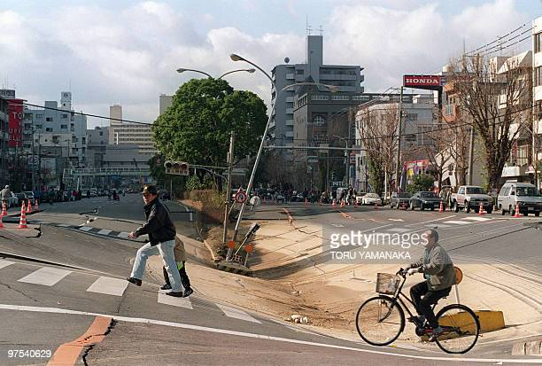 Residents pass 19 January 1995 in Kobe the steep incline of a depression on Kirai Dori street formed when the subwaytrain tunnel collapsed underneath...