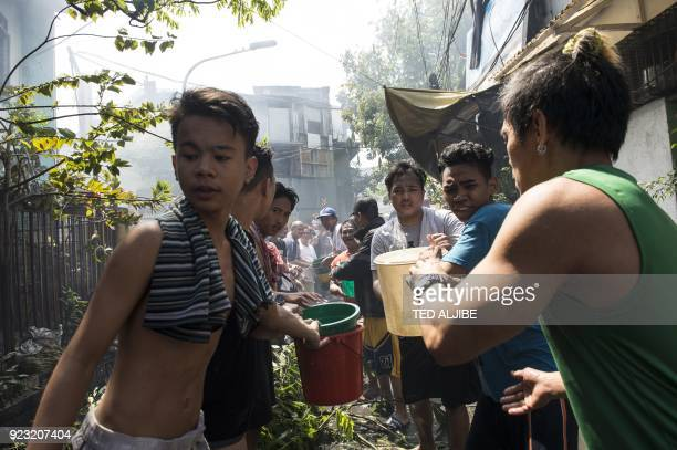 Residents pass around plastic buckets filled with water as they help firefighters in putting out a fire that hit a residential area in Manila on...
