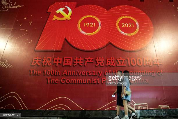 Residents pass by a sign celebrating the centenary of the Chinese Communist Party in street on June 25, 2021 in Wuhan, Hubei. China. With no recorded...