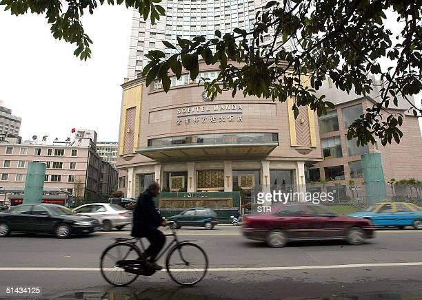 Residents pass by the Sofitel Wanda hotel in Chengdu southwestern China's Sichuan province 07 October 2004 where French President Jacques Chirac will...