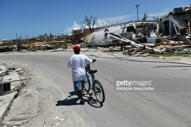 TOPSHOT Residents pass damage caused by Hurricane Dorian on September 5 in Marsh Harbour Great Abaco Island in the Bahamas Hurricane Dorian lashed...