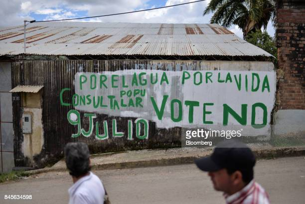 Residents pass in front of a graffiti encouraging residents to vote against an oil project to protect the environment in the town of Arbeleaz...