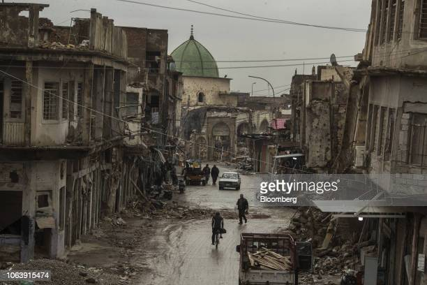 Residents pass in front of damaged buildings in the Old City of Mosul, Iraq, on Tuesday, Nov. 6, 2018. More than a year after the brutal fighting...