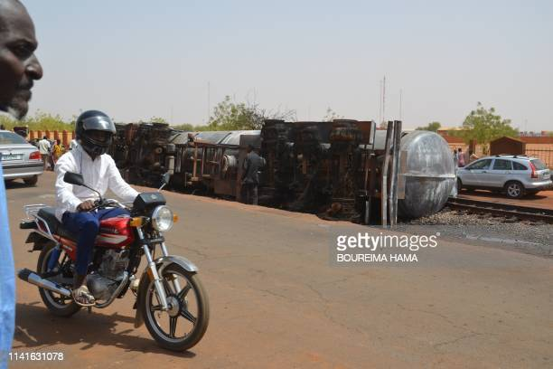 Residents pass near the calcined tanker truck after an explosion which killed more than 55 people near the airport of Niamey on May 6 2019 Fiftyfive...