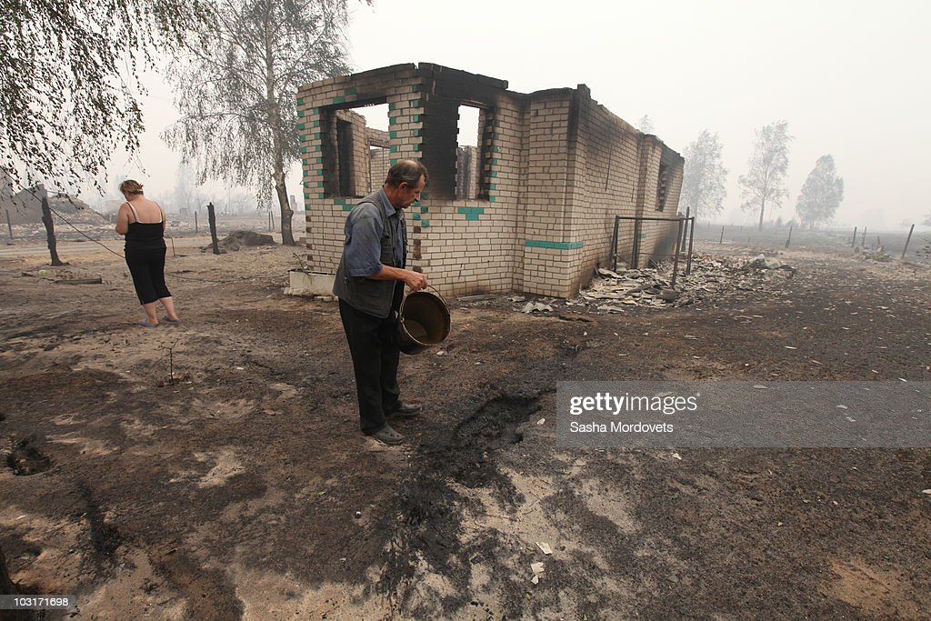 Residents pass through a village burnt by a forest fire on July 30, 2010 in Verkhnyaya Vereya, Russia. Putin visited the village where all 341 homes have burned to the ground. The Kremlin called the army to help assist as fires rage over 214,136 acres throughout vast sections of Russia. A state of emergency was ordered on Friday as firefighters continued to save cillages and forerests from the blaze.