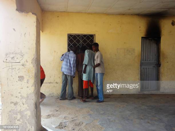 Residents peep througth the window of the locked off Haye dispensary on February 8 2013 in the northern Nigerian city of Kano where gunmen on...