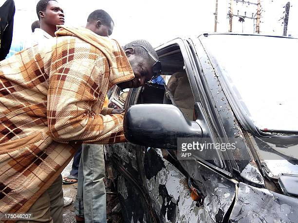 A residents peers through the shattered widow of a badlydamaged car at the scene of an explosion targeting an openair beer garden at Enugu Road in...